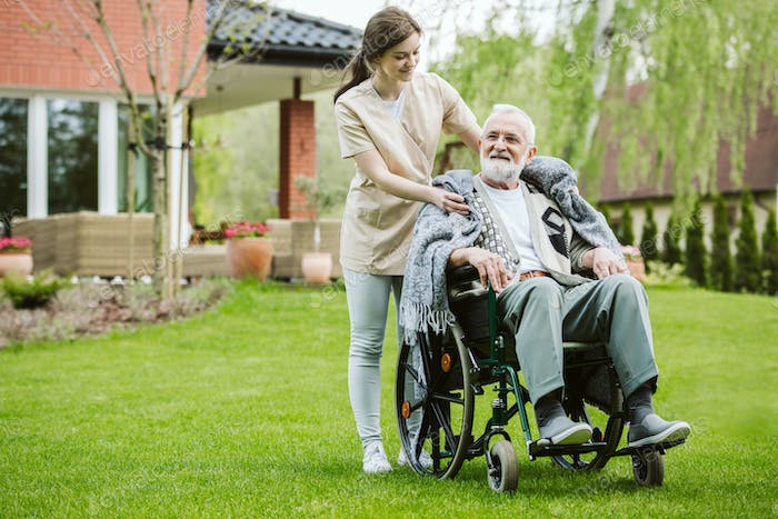 Senior man with helpful volunteer in the garden of professional care home