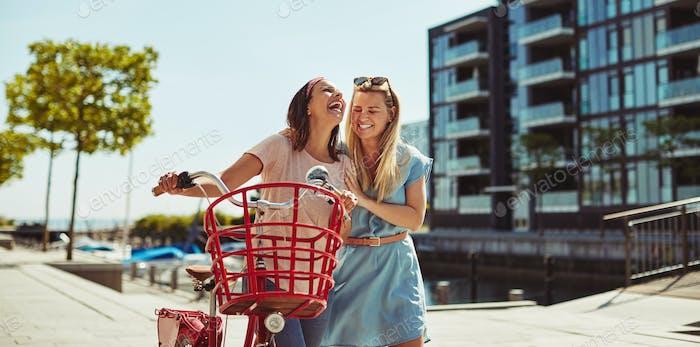 Lachende junge Freunde zu Fuß mit ihrem Fahrrad in der Stadt