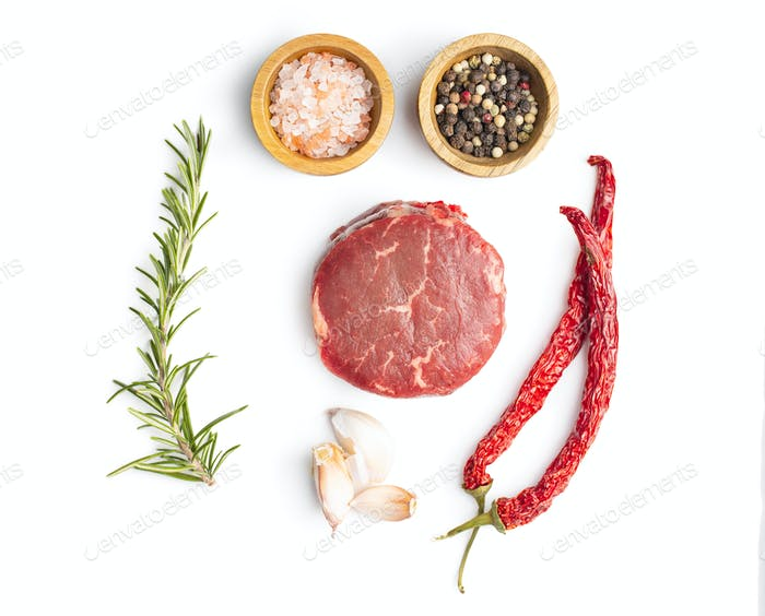 The raw beef meat steak with garlic, rosemary, salt and pepper