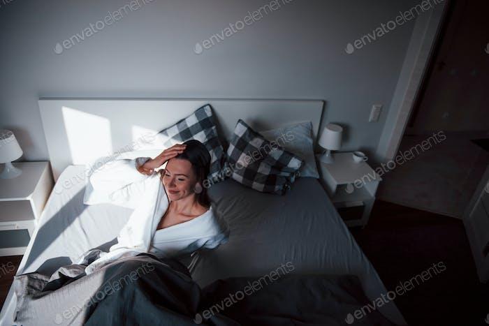 Glückliches Mädchen. Hübsche junge Frau liegt morgens auf dem Bett in ihrem Zimmer