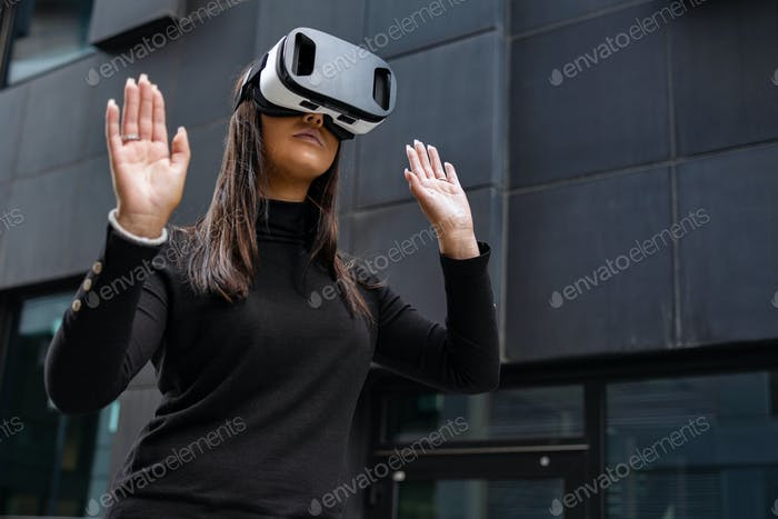 Woman Playing With Virtual Reality Glasses Against Futuristic Wall
