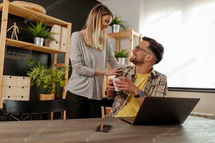 Schöne Frau, die ihrem Mann mit einem Lächeln einen Kaffee trägt.