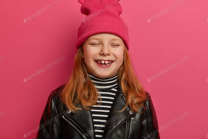 Headshot of pretty ginger girl has playful upbeat expression, closes eyes and laughs out happily, ha