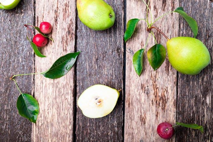 Birne und kleiner Apfel auf rustikalem Holzhintergrund. Draufsicht. Gestell Herbsternte.