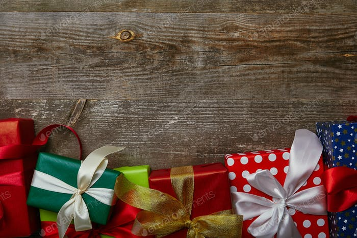 flat lay with presents wrapped in different wrapping papers with ribbons on wooden background