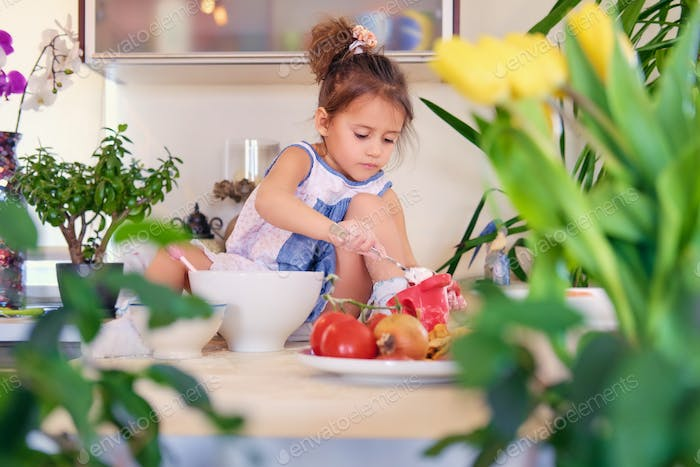 Little girl sits on a table in a kitchen and try to make diet porridge.