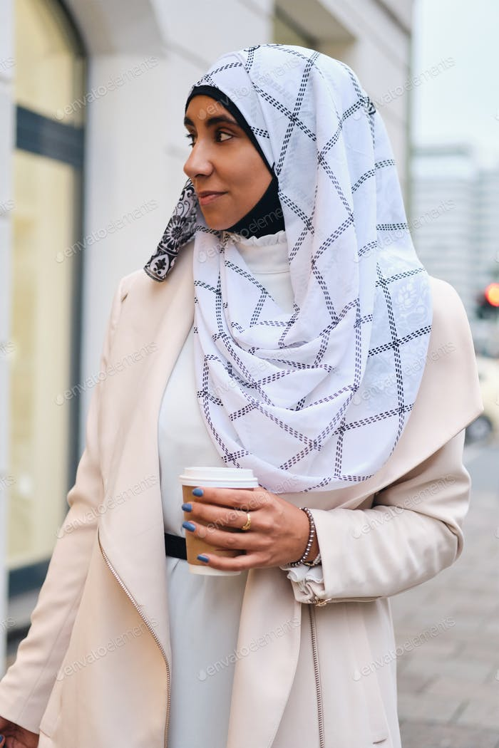 Young attractive Arabic woman in hijab walking through city with coffee