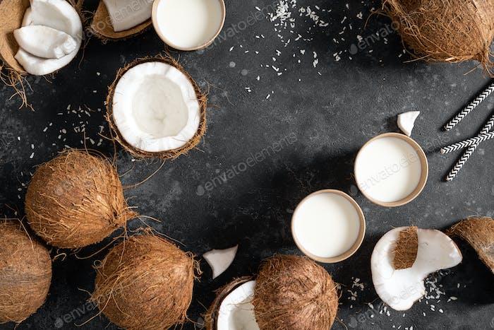 Kokosmilch, ganze und rissige Kokosnüsse auf schwarzem Hintergrund, Draufsicht