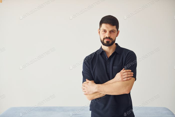 Serious man in shirt standing indoors against white background