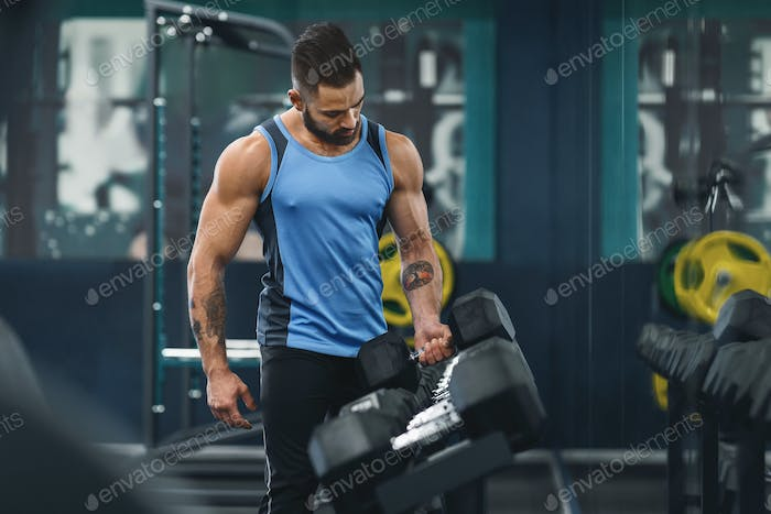 Strong bodybuilder choosing weight of dumbbell for training