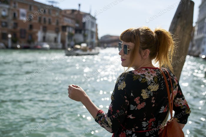 Caucasian redhead woman with floral dress looking at grand canal Venice