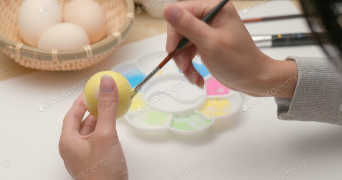 Coloring eggs for Easter with hands and a brush with watercolor paints