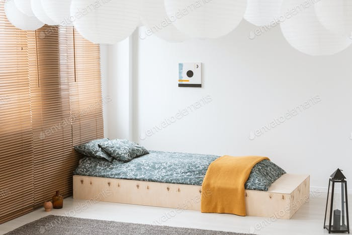 Orange blanket on wooden bed in white bedroom interior with lant
