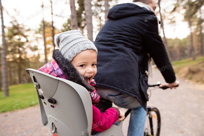 Unrecognizable father and daughter cycling in autumn park