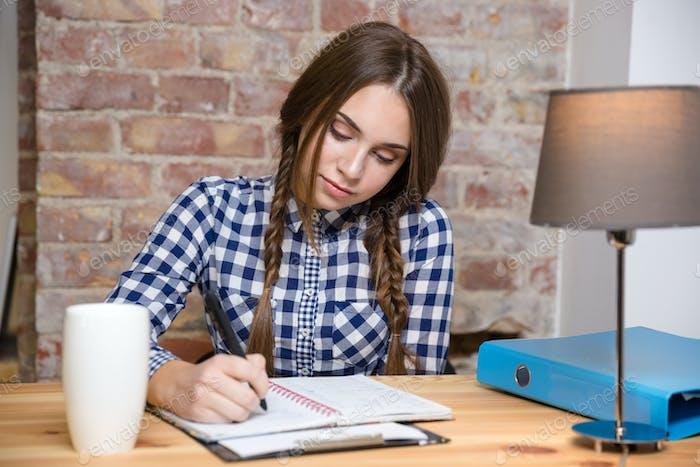 Frau macht ihre Hausaufgaben zu Hause