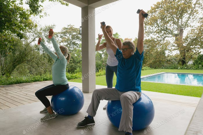 Caucasian female trainer assisting active senior couple to exercise with dumbbell in the porch