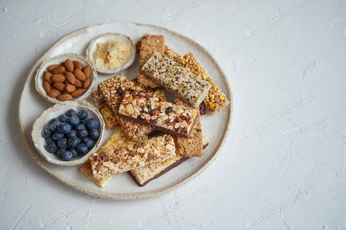 Mixed composition of energy nutrition bar, granola on ceramic plate over white background