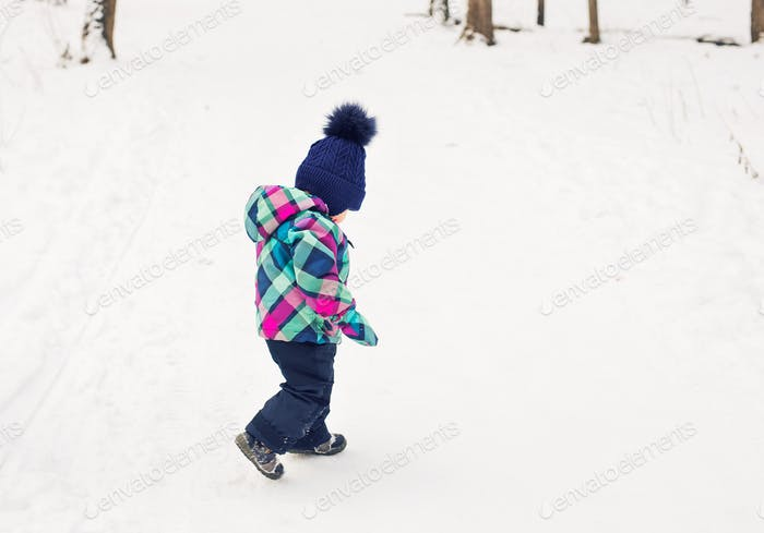 Happy toddler girl playing in a beautiful snowy winter park on Christmas day