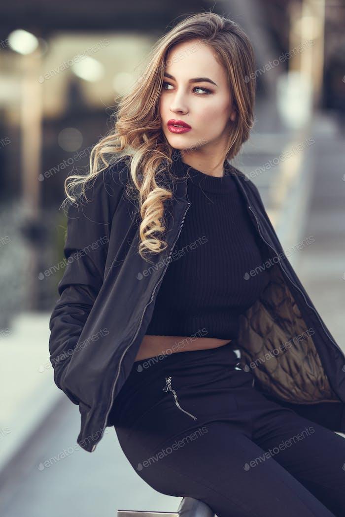 Hermosa joven con chaqueta negra sentada en la calle.