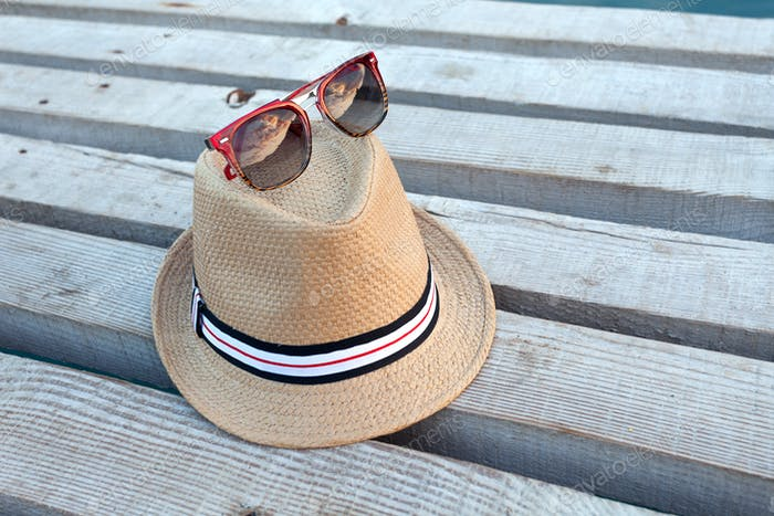 Sunglasses and hat on the wooden texture in summer