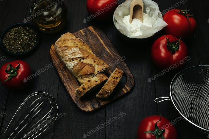 Fresh baked bread and baking ingredients on a table