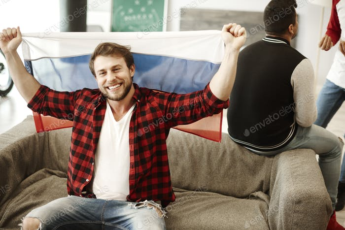 Happy football fans waving a russian flag