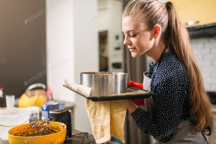 Woman cook in apron holds hot pan with fresh cake