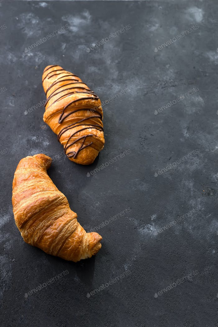 freshly baked croissant decorated with chocolate sauce isolated on a black slate