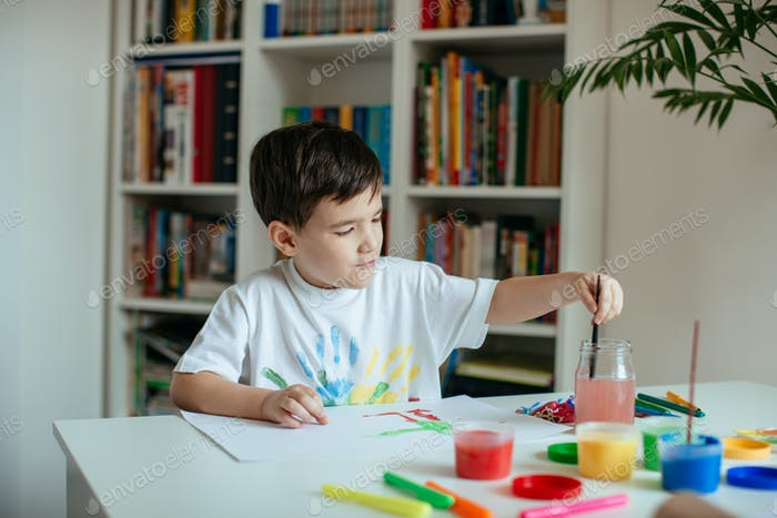 Cute 5 year old boy enjoying painting with watercolor.