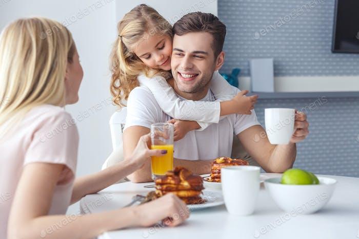 hermosa familia desayunando y jugando en la mañana de fin de semana