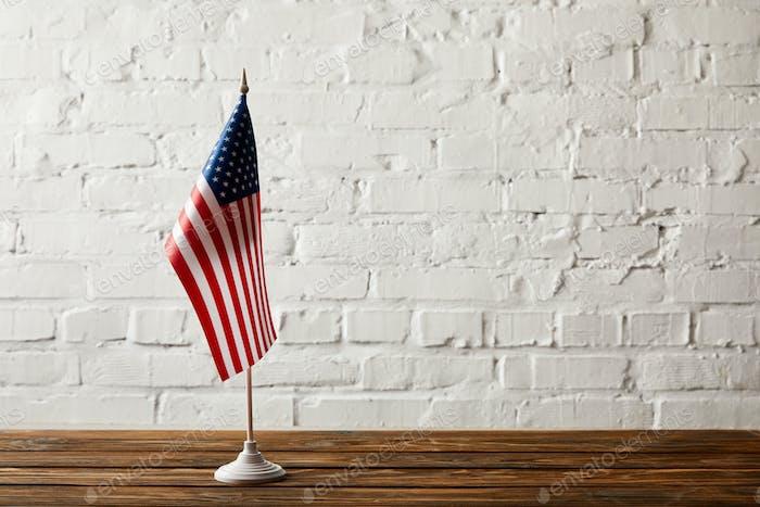asta de bandera de los Estados Unidos de América sobre superficie de madera contra pared de ladrillo