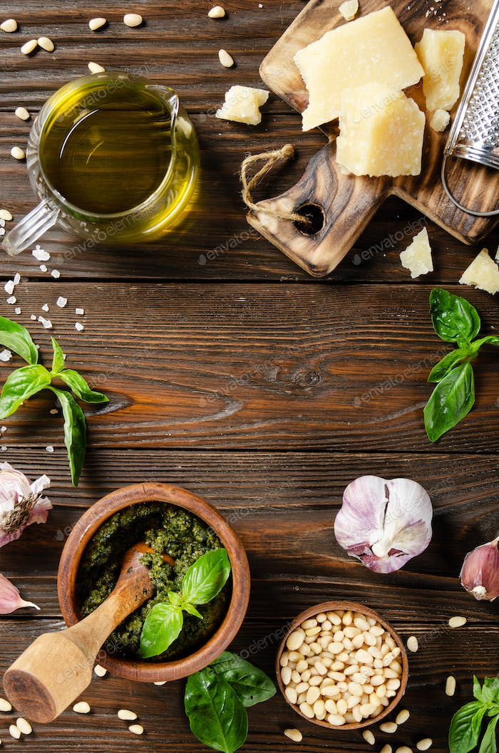 pesto sauce in wooden mortar and its ingredients on kitchen table