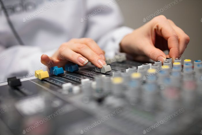 Midsection Of Radio Host's Hands Using Music Mixer In Studio