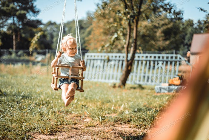 Little boy playing on swing in backyard at coutryside