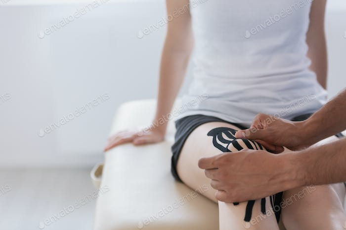 Physical therapist and sportwoman during kinesiotaping therapy