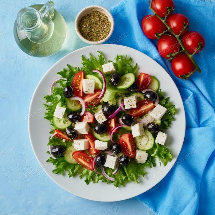 Griechischer Salat auf weißem Teller auf hellblauem Tisch, Draufsicht