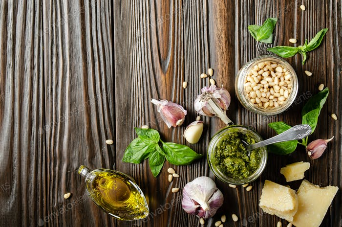Flat lay view at food background of genovese pesto sauce and its ingredients. Space for text