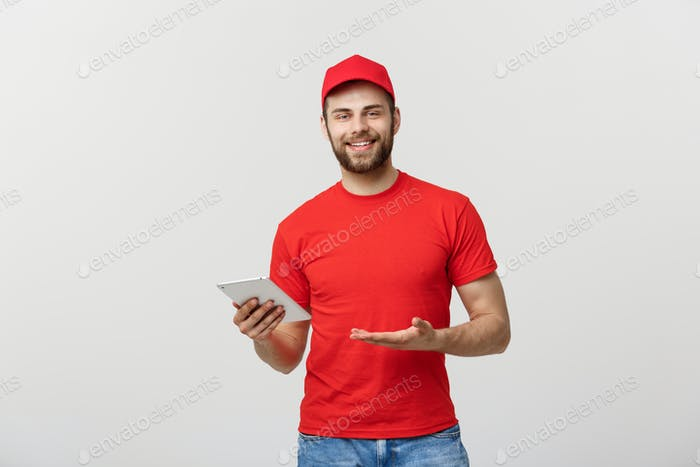 Smiling delivery man with tablet in studio. isolated gray background