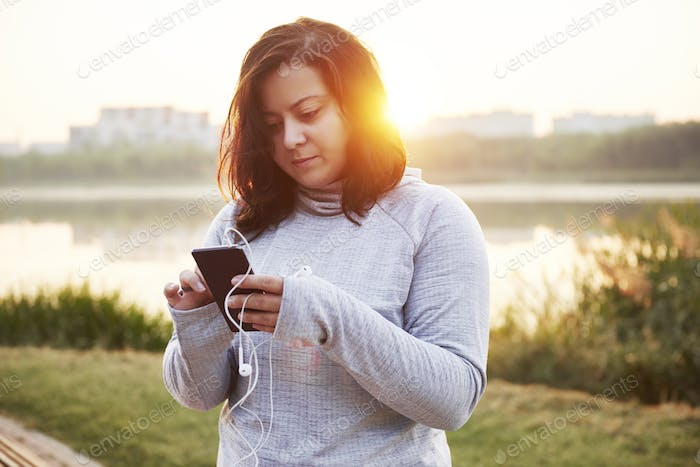 Female athlete using a mobile phone in public park