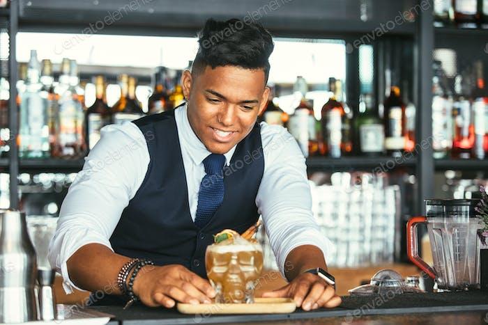 Smiling bartender presenting a cocktail