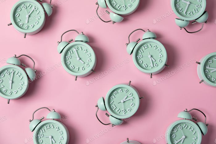 Creative layout of green alarm clock's on pastel pink background. Minimal concept.