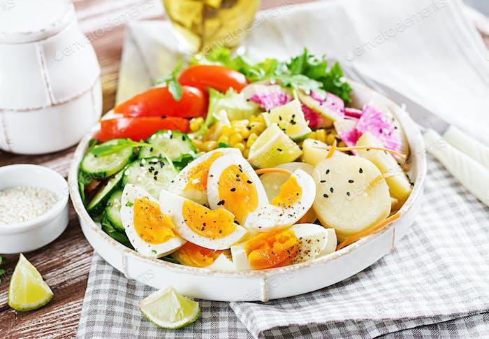 Fresh salad. Bowl with fresh raw vegetables - cucumber, tomato, watermelon radish