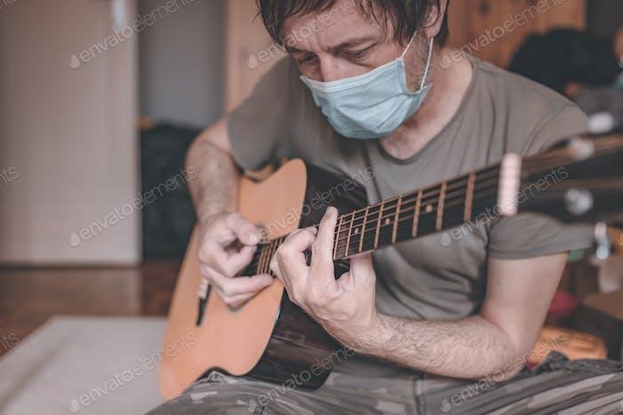 Mann spielt akustische Gitarre in Hausquarantäne Selbstisolierung