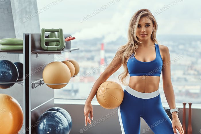 Sexy girl with a fitness ball in the gym.