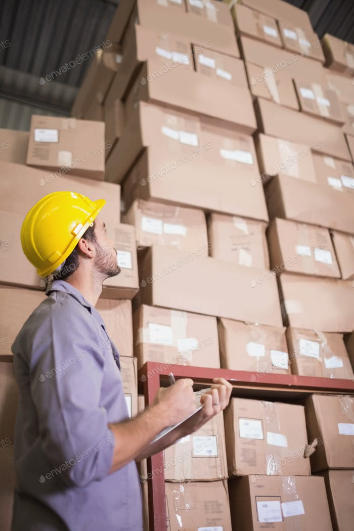 Warehouse worker with clipboard in warehouse