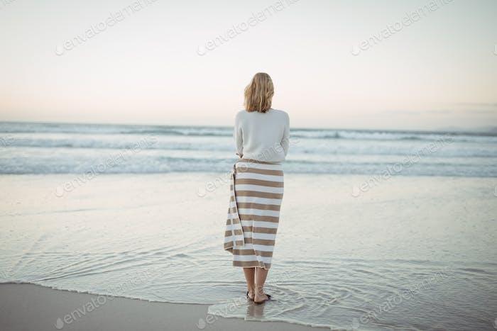 Rückansicht von Frau am Strand während der Dämmerung