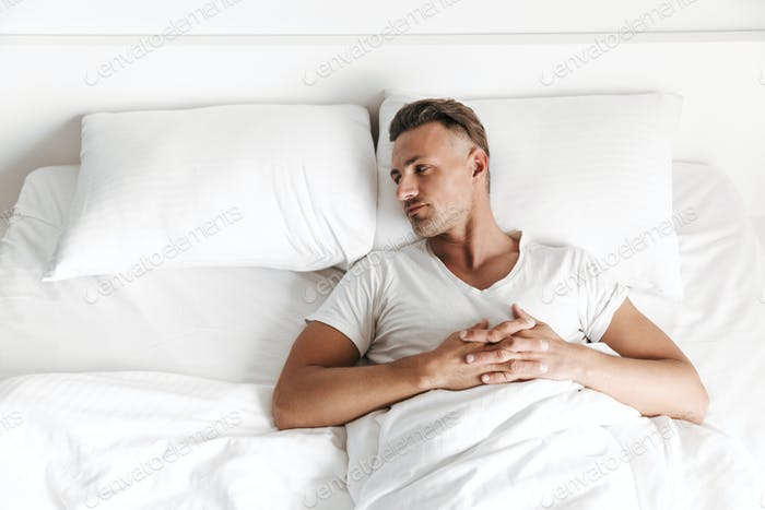 Upset man laying in bed and looking away