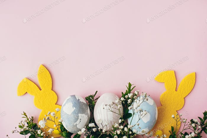 Stylish easter eggs, yellow bunny on pink paper table flat lay
