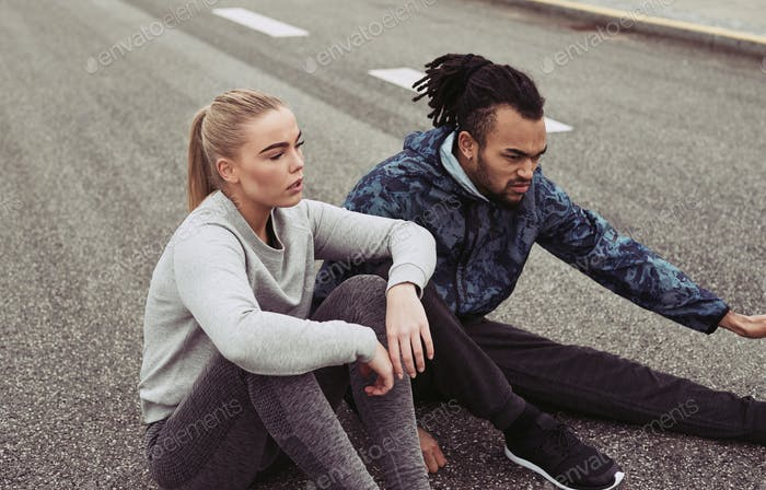 Tired young couple catching their breath during an outdoor run