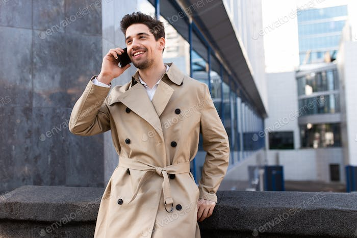 Young attractive stylish man in trench coat happily talking on cellphone on street